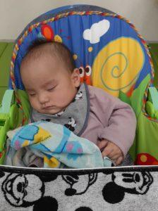 赤ちゃん向けの玩具で遊んで眠る